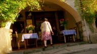 Slow motion canted wide shot rear view senior woman entering cafe with outdoor tables / Provence, France