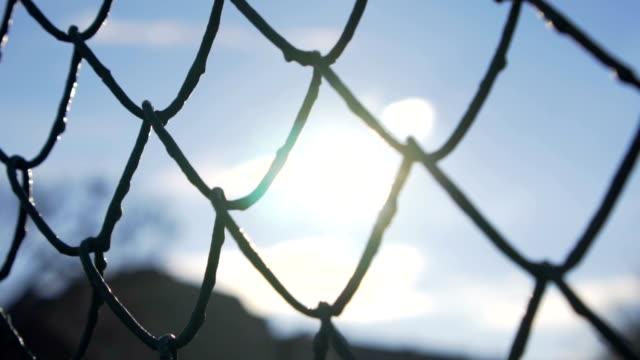 Slow motion: Chain Fence Against Golden Sun