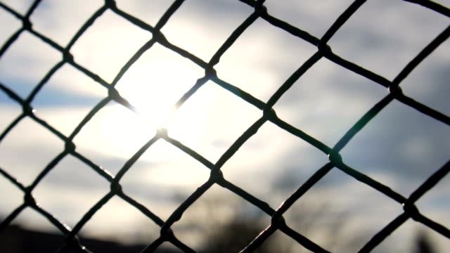 Slow motion: Chain Fence Against Golden Sun