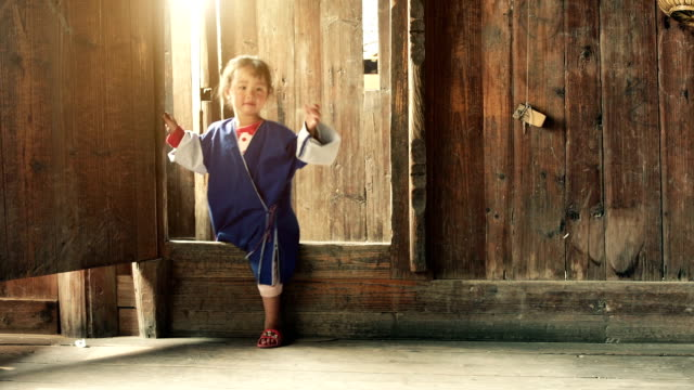 Slow motion: Chinese female child walking into a wooden house