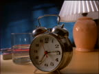 slow motion close up alarm clock rings; woman's hand fumbles to turn it off, clock falls