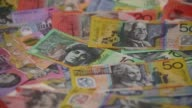 Slow Motion close up Australian dollar banknotes of various denominations are added to a pile arranged in a white background for a photograph in...