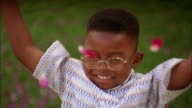 Slow motion close up Black boy w/glasses smiling and throwing flower petals in air