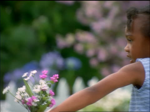 slow motion close up Black girl handing flowers to mother + hugging her outdoors
