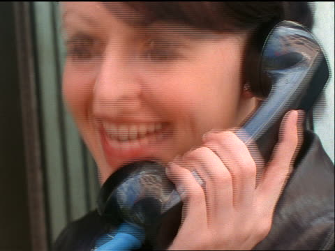 slow motion close up brunette woman talking + smiling on pay phone outdoors / gets angry