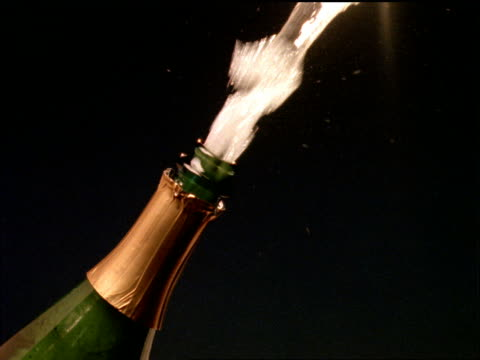 slow motion close up cork explodes from champagne bottle