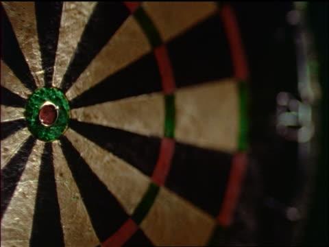 slow motion close up dart hitting bullseye on dart board
