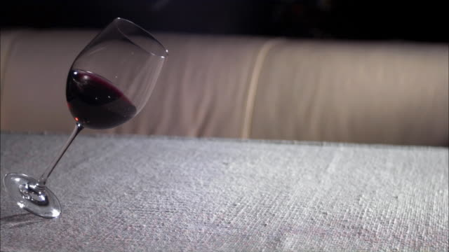 Slow motion close up dolly shot glass of red wine falling on table and spilling on runner