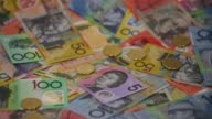 Slow Motion close up dropped one dollar coins bounce over Australian dollar banknotes of various denominations arranged for video in Sydney Australia...