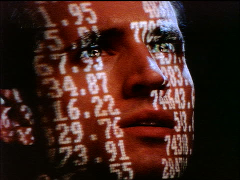 slow motion close up face of man with numbers projected onto him / turns head towards camera