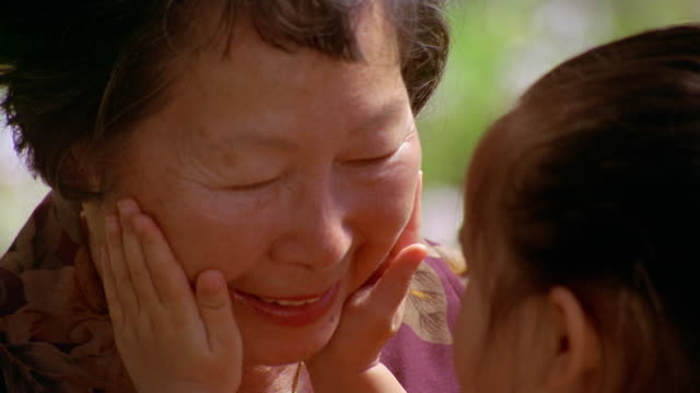 Slow motion close up grandmother smiles as granddaughter holds and kisses her face outdoors