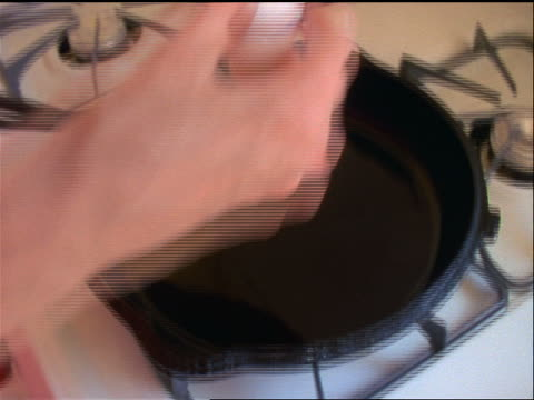 slow motion close up hands of woman breaking egg into cast iron frying pan