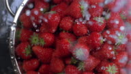 Slow motion close up high angle water sprinkling pile of strawberries