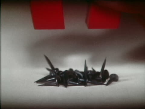 1961 slow motion close up nails rising up and sticking to red magnet