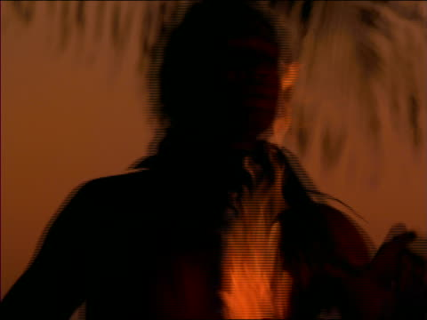 slow motion close up native man dancing with fire at dusk / Hawaii