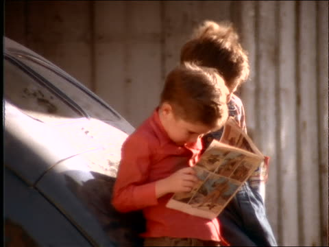 slow motion close up of 2 boys reading comic book / start fighting
