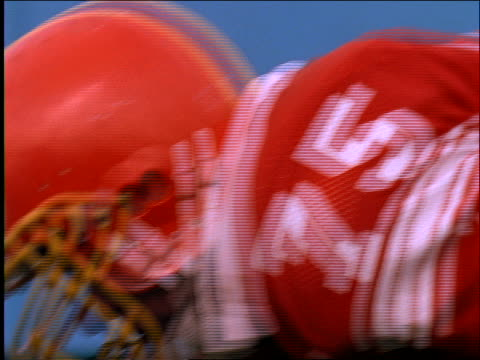 slow motion close up of 2 football players tackling each other
