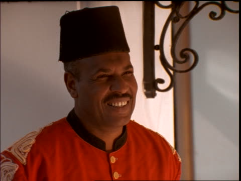 slow motion close up of bellhop in fez talking + smiling at camera / Egypt