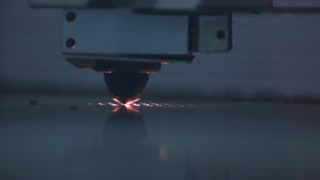Slow motion close up of laser cutter as it punches holes in a sheet of metal.