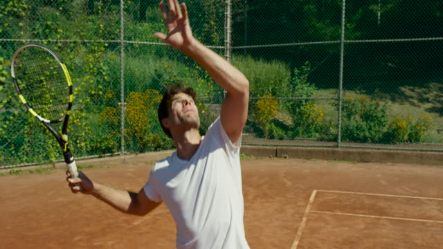 Slow motion close up of man bouncing tennis ball on clay court before serving