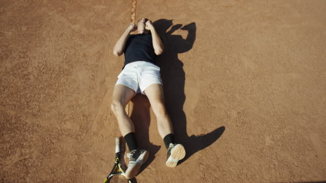 Slow motion close up of serious man on clay court who then falls to the dirt while celebrating