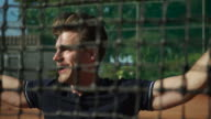 Slow motion close up of smiling young man behind tennis court net
