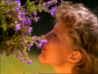 slow motion close up of woman smelling bunch of picked flowers