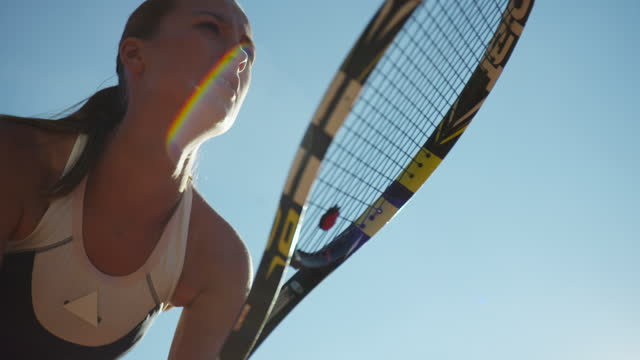 Slow motion close up of young woman's face behind tennis racket