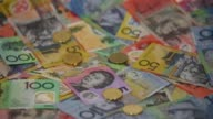 Slow Motion close up one dollar coins are dropped on top of Australian dollar banknotes of various denominations arranged for video in Sydney...