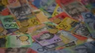 Slow Motion close up one dollar coins are dropped over Australian dollar banknotes of various denominations arranged for video in Sydney Australia on...