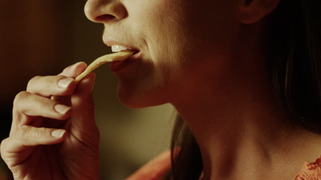 Slow motion close up panning shot of woman biting into pita chip / Cedar Hills, Utah, United States