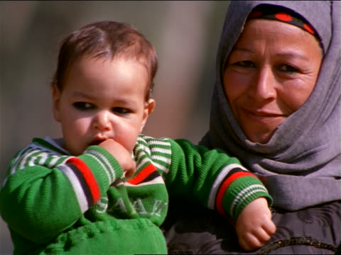 slow motion close up PORTRAIT Egyptian woman wearing scarf on head holding baby smiling outdoors / Egypt