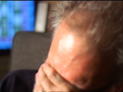 slow motion close up PORTRAIT middle-aged man sitting indoors laughing + covering mouth with hand