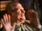 slow motion close up PORTRAIT seated middle-aged man laughing + gesturing to stop indoors