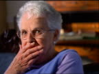 slow motion close up PORTRAIT seated senior woman with eyeglasses looking shocked + covering mouth indoors