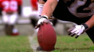 slow motion close up PROFILE football player kicking ball being held by second player / NFL logo on ball