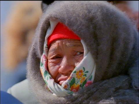 slow motion close up senior woman wearing babushka + shawl around head turning to look at camera / Russia