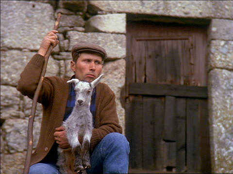 slow motion close up shepherd holding small goat in front of stone cottage / they both turn heads / Portugal