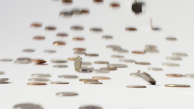 Slow motion close up shot of rolling and sliding coins / Cedar Hills, Utah, United States