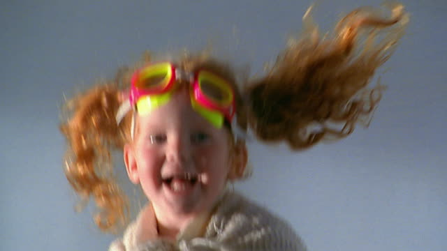 Slow motion close up small redhead girl bouncing / zoom out to wide shot girl jumping on parents' bed / falling down