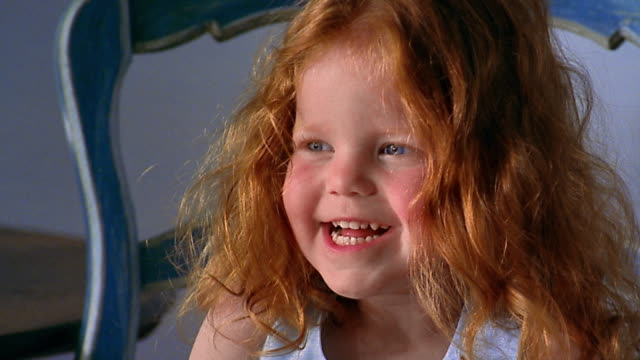 Slow motion close up small redhead girl / tilt down hands holding round box / tilt up face laughing