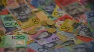 Slow Motion close up tossed one dollar coins bounce over Australian dollar banknotes of various denominations arranged for video in Sydney Australia...