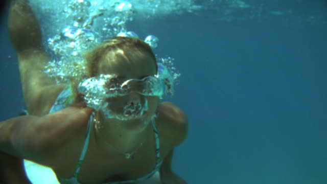 Slow motion close up woman diving onto surfboard beneath surface of water / air bubbles from nose