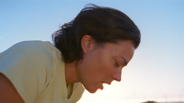 Slow motion close up woman resting after finishing long run/ woman looking up to sky/ tilt up sky/ California