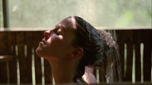 Slow motion close up woman rinsing hair in outdoor shower / The Amazon, Brazil