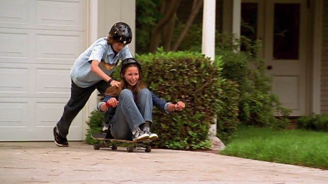 Slow motion close up zoom out zoom in girl sitting and boy standing behind her riding on skatebaord in driveway