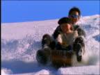 slow motion couple riding toboggan down hill toward camera