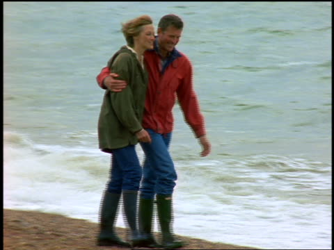 slow motion couple walking on beach in boots + windbreakers / Brighton, England