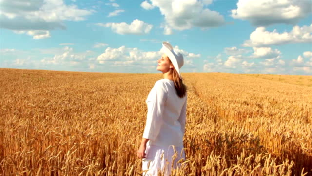 Slow Motion: Crane Shot Of Young Woman In Wheat Field