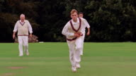 slow motion cricket bowler running + pitching ball on field / two fielders in background / Hertfordshire, England